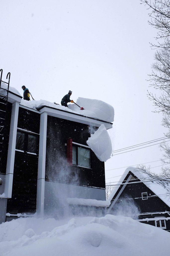 Clearing snow off roofs in Niseko, Japan