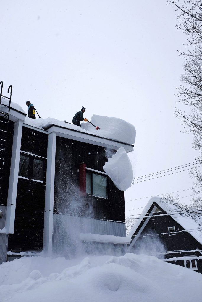 Clearing snow off roofs in Niseko, Japan